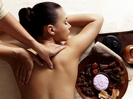 Massage Ayurvédique au niveau des contours des omoplates d'une femme allongée sur le ventre à Mours proche de l'Isle-adam.