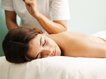 Massage lomi-lomi avec le coude sur le dos d'une femme allongée sur le ventre à Mours proche de l'Isle-adam