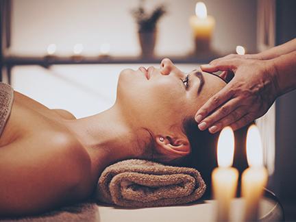 """Massage crânien intitulé """"Tête dans les étoiles"""" sur une femme allongée sur la table de massage au Global Fitness à Mours"""