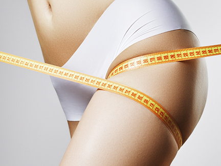 Une femme mesure son tour de cuisse avec un mètre pour constater le résultat de son massage amincissant